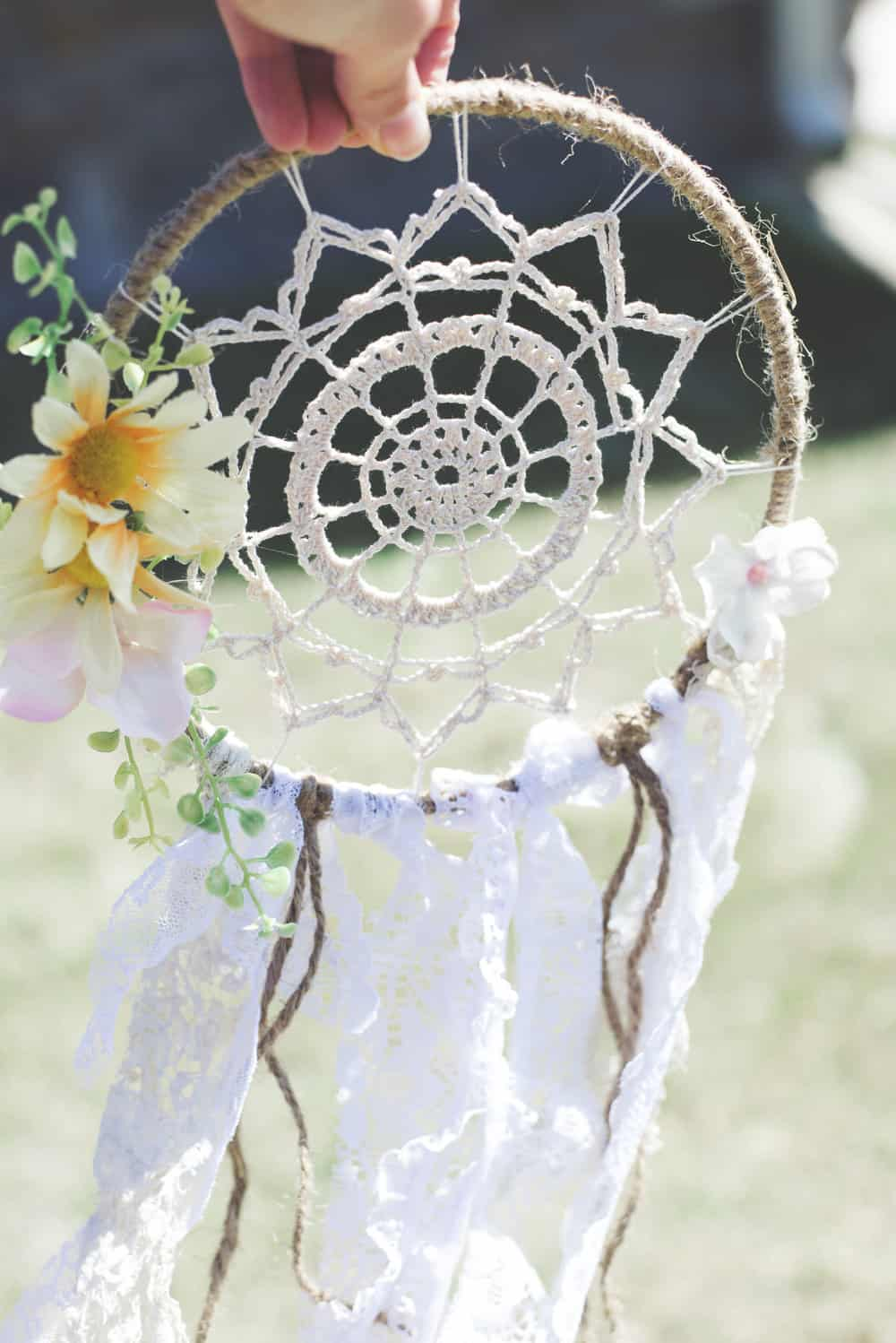 Picture of a dreamcatcher with the centre web made from crochet, with spring flowers on the side and lace tails