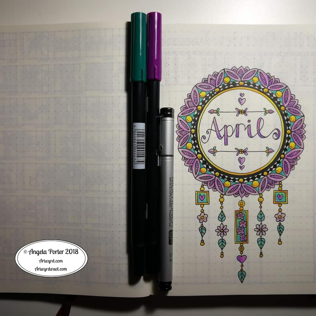 A photo of an April cover page for a Bullet Journal that has a dreamcatcher illustration coloured with purple, yellow and green which says April in the middle