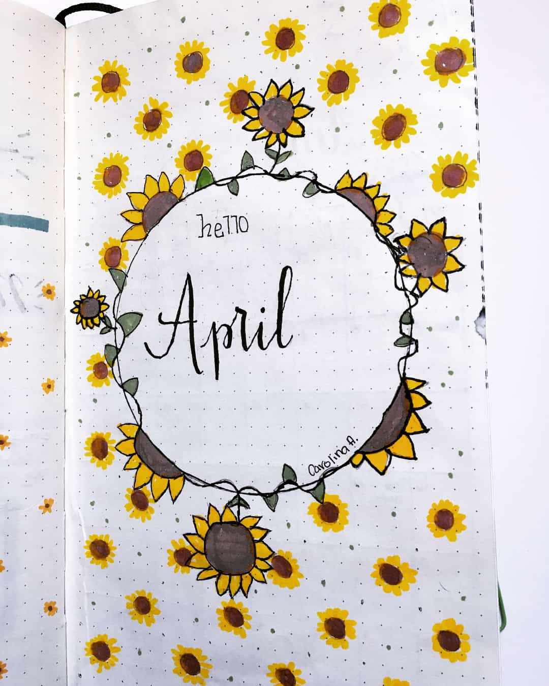 A photo of a cover page for a Bullet Journal that says Hello April and is decorated with sunflowers