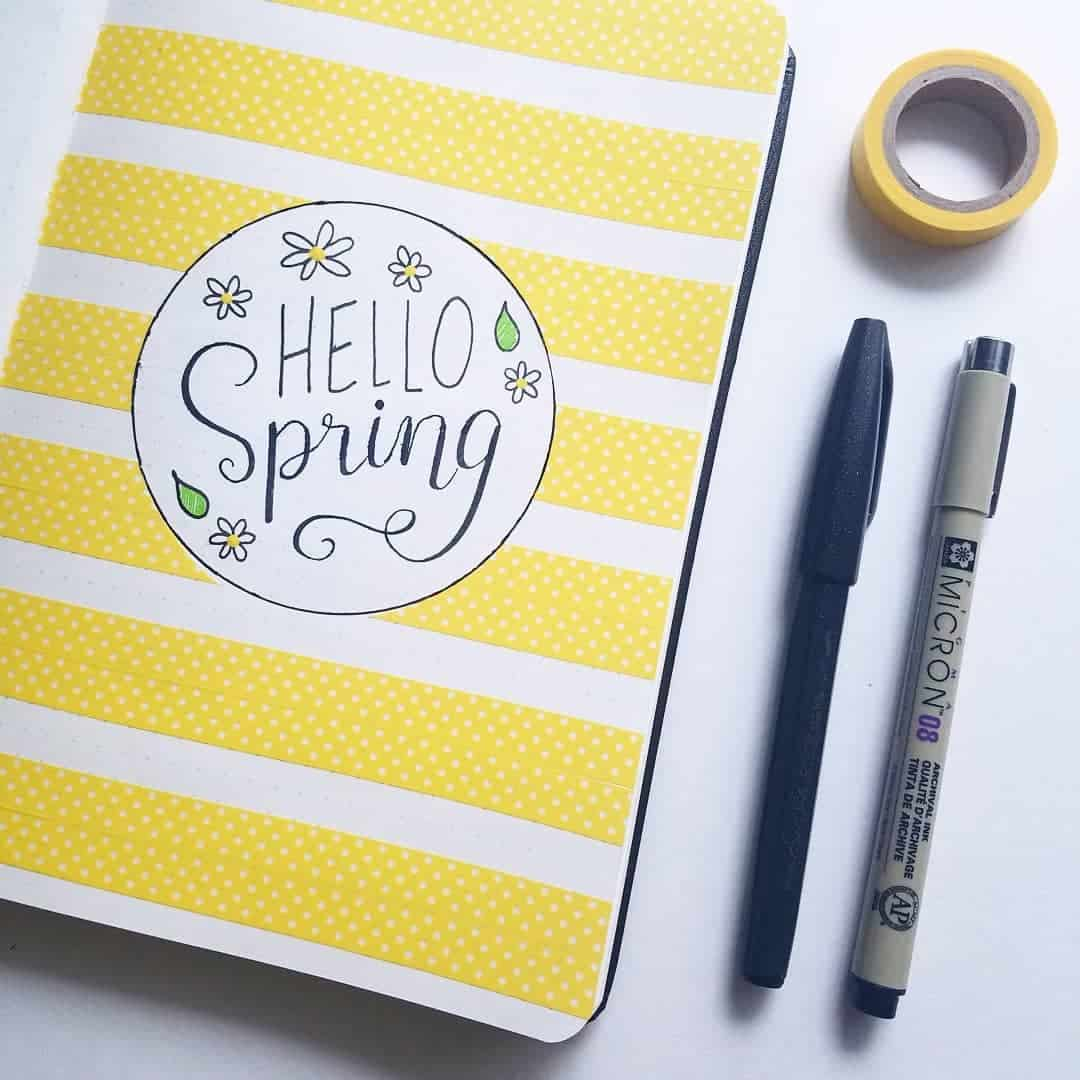 A photo of a Bullet Journal cover page that says Hello Spring with yellow washi tape in stripes for the background