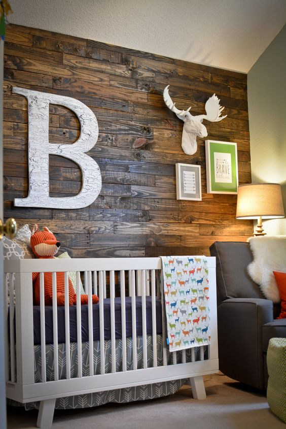 A reclaimed wood accent wall makes this a modern rustic nursery