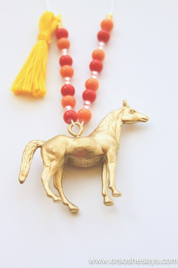 Gold painted horse charm hanging at the end of a beaded necklace complete with a tassel