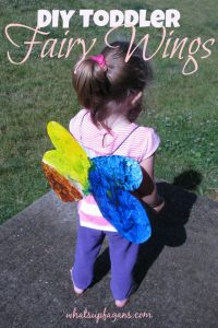 A toddler wearing a set of beautiful fairy wings that have been cut out from a cereal box and then painted on both side