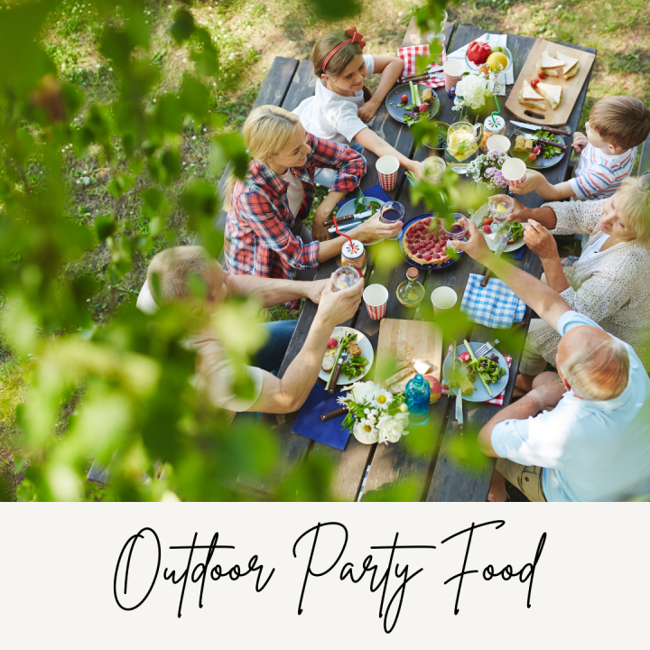 A photograph of people enjoying an outdoor party with lots of food