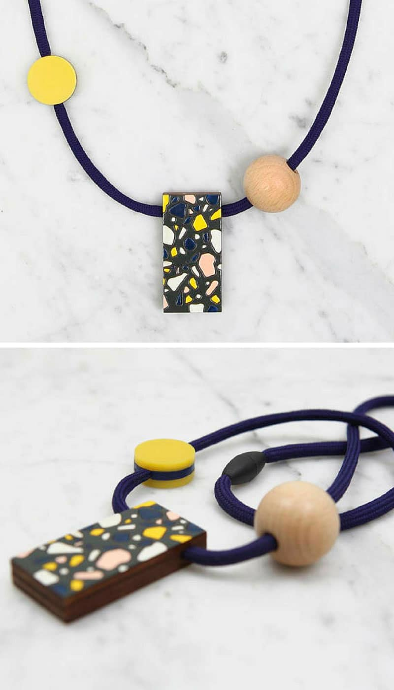 Striking contemporary geometric inspired necklace made up of a large birch plywood rectangle, featuring a hand-painted and varnished terrazzo pattern in blue / white / yellow / pink on an dark grey background, a smaller yellow acrylic circle with a large wooden bead all on a dark blue cord.